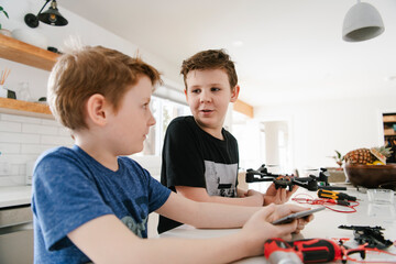 Brothers with digital tablet learning to assemble drone in kitchen