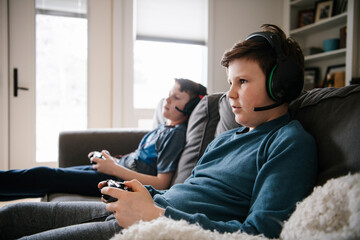 Brothers with headsets playing video games on living room sofa