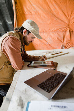Male carpenter using digital tablet in woodworking workshop