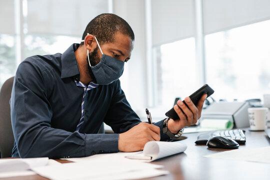 Mature man wearing mask using phone and writing
