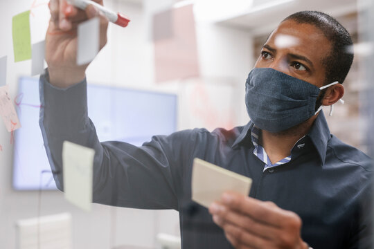 Man wearing face mask writing on sticky notes