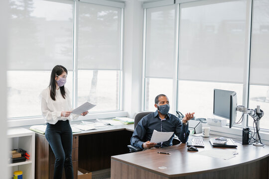 Colleagues wearing face masks in office