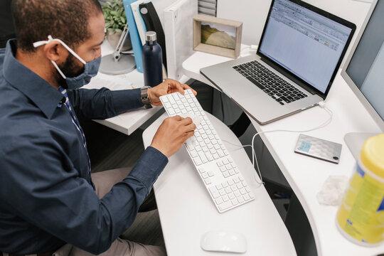 Man wearing facemask sanitizing computer keyboard