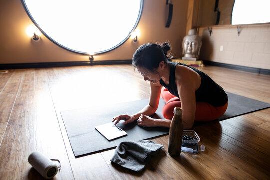 Female yoga instructor using digital tablet on mat in studio