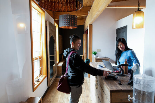 Yoga student paying with smart phone at front desk