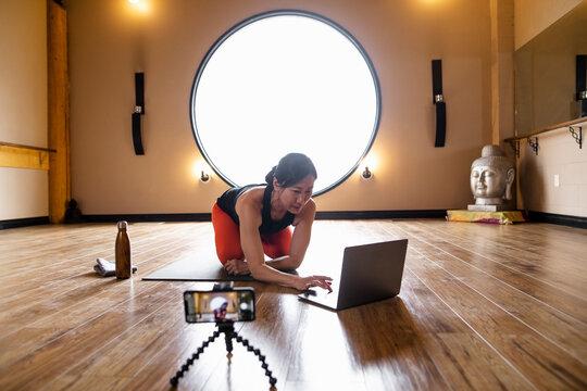 Female yoga instructor preparing to teach online class in studio