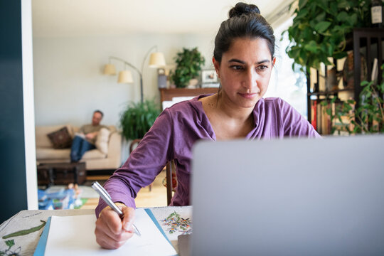 Woman working from home at laptop in dining room