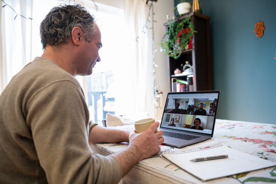 Man with laptop video conferencing with colleagues from home