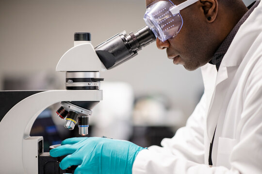 Medical researcher wearing goggles using microscope in laboratory