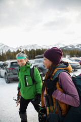 Smiling couple carrying snowshoeing equipment in ski resort parking lo