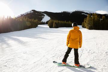 Male snowboarder on sunny snowy mountain ski slope