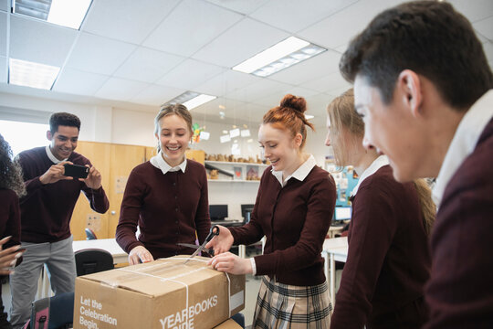 Excited high school students opening yearbook box in classroom