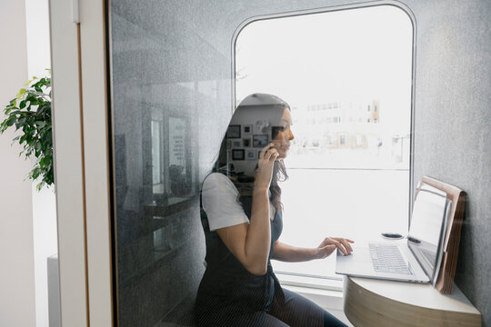 Woman using laptop in office phone booth