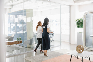Two women walking in modern office
