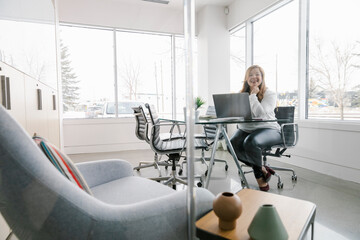 Woman sitting at desk using laptop in office