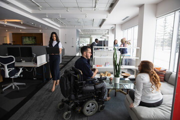 Man in wheelchair discussing with colleague