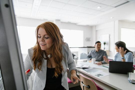 Woman using whiteboard in creative office