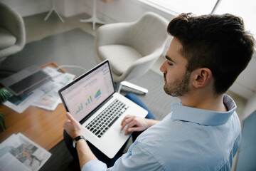 High angle of businessman using laptop