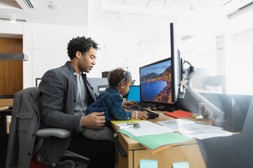Father working on computer with girl on lap