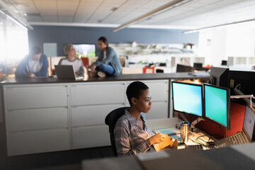 Woman eating food at desk in office