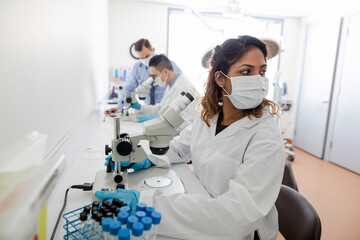 Medical scientist using microscope in clinic