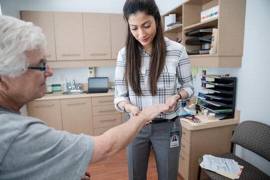 Doctor examining hand of senior patient in clinic exam room