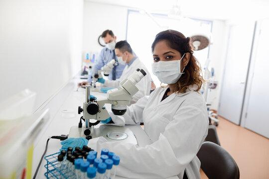 Portrait female medical scientist using microscope in clinic