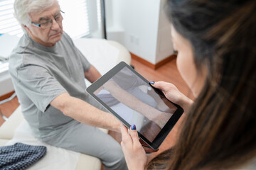Doctor with digital tablet photographing arm of senior patient