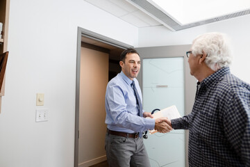 Male doctor greeting and shaking hands with senior patient in clinic