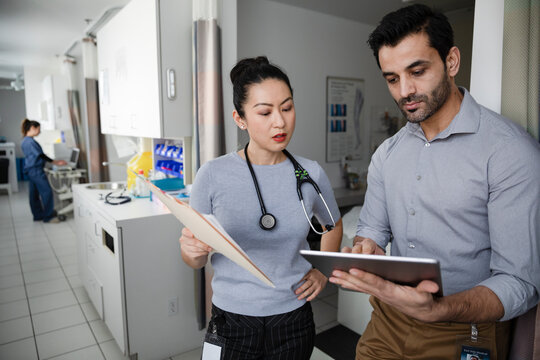 Doctors with digital tablet and medical chart consulting in clinic