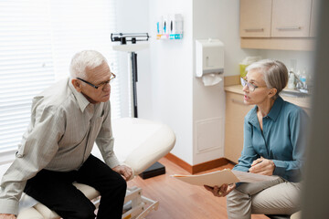 Senior doctor and patient discussing medical chart in clinic exam room