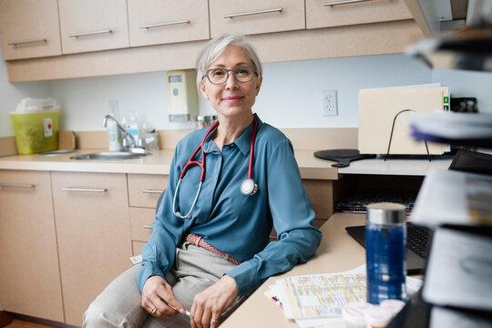 Portrait confident smiling female senior doctor in clinic exam room
