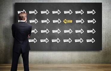 businessman looking at a chalkboard with an arrow symbol that is different from all others