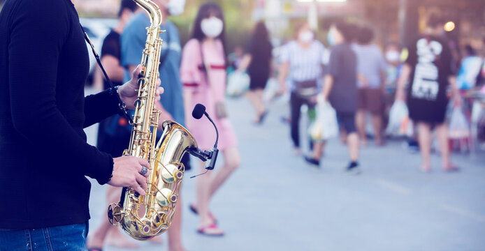 A street musician plays the saxophone and wearing face shield with blurry many people wearing mask and walking in Bangkok, Thailand.