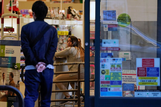 A Rite Aid store worker monitors people entering the store in downtown Los Angeles