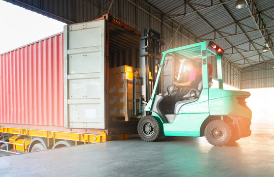 Forklift loading cargo shipment pallet goods into a truck container at dock warehouse. Cargo freight industry delivery warehouse logistics transportation.