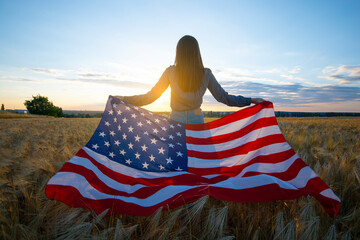 Girl with the flag of America at the wheat field against the sunset