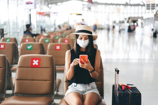 Young adult tourist woman wear mask for virus outbreak at airport terminal with social distancing chair.
