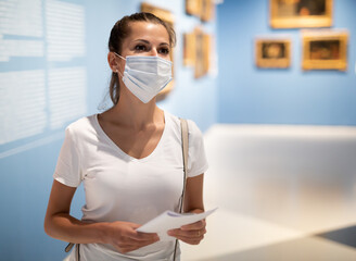 Young woman wearing face mask observing artworks in museum, new normal due to coronavirus outbreak