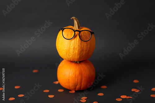 halloween and holiday concept - halloween pumpkins with glasses