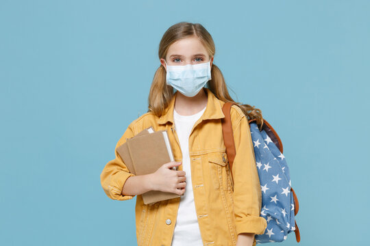 Little kid schoolgirl 12-13 years old in sterile face mask backpack isolated on blue background. Epidemic pandemic rapidly spreading coronavirus 2019-ncov sars covid-19 flu virus concept. Hold books.