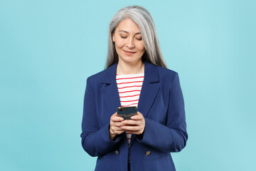 Smiling gray-haired business woman in blue suit posing isolated on pastel blue background studio....