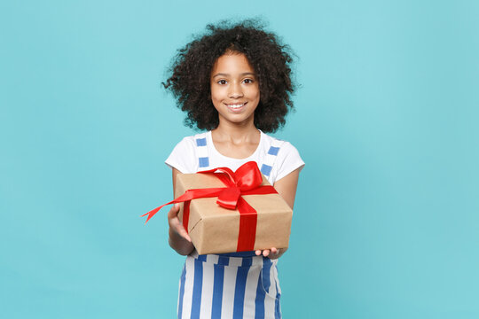 Smiling little african american kid girl 12-13 years old in striped clothes isolated on blue background. International Women's Day birthday, holiday concept. Hold red present box with gift ribbon bow.