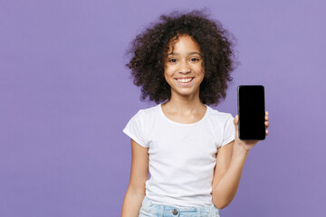 Smiling little african american kid girl 12-13 years old in white t-shirt isolated on violet wall...