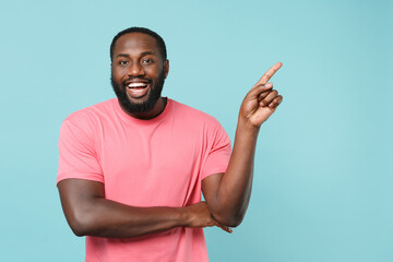 Cheerful young african american man guy in casual pink t-shirt isolated on blue wall background...