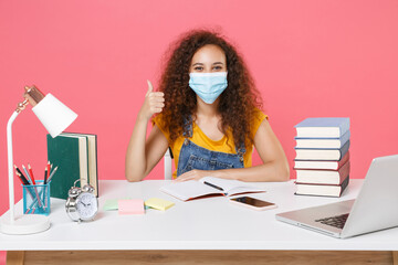 African american girl in sterile face mask employee in office work at desk isolated on pink...