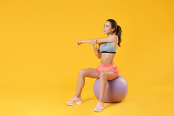 Full length portrait beautiful young fitness sporty girl in sportswear working out isolated on yellow background. Workout sport motivation lifestyle concept Sit on fitball doing stretching exercising.