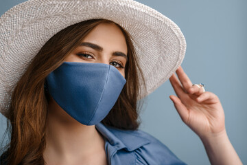 Woman wearing stylish protective face mask, summer white hat, posing on blue background. Trendy Fashion accessory during quarantine of coronavirus pandemic. Close up studio portrait.