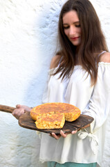 Woman displaying freshly baked Spanish tortilla