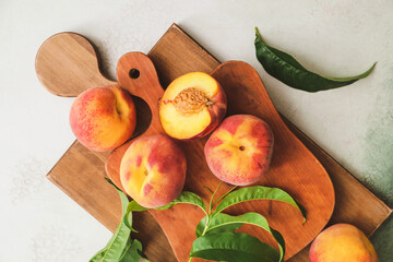Boards with ripe peaches on light background
